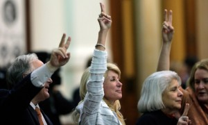 wendy-davis-holds-up-two-fingers-to-signal-a-no-vote-as-the-session-she-tried-to-filibuster-draws