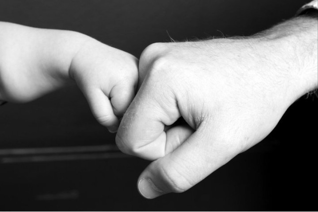 father and son fist bump