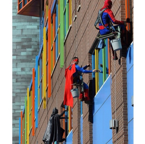 Superheroes wash window at Children's Hospital